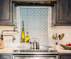 Sophisticated galley kitchen with patterned tile over stove by Obelisk Home