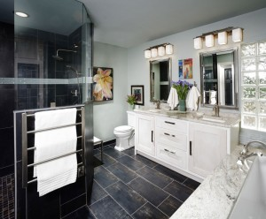 Master bathroom with dark gray tile and white cabinets
