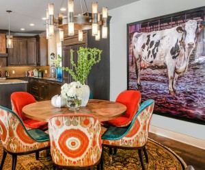 Dining room with round table with bold dining chair and original art by Jared Gillett, design by Obelisk Home