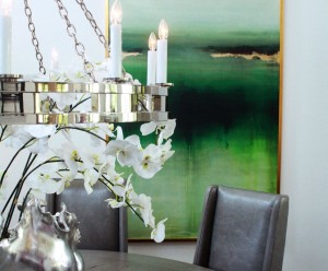 Dining room with contemporary style, a silver chandelier and emerald green artwork